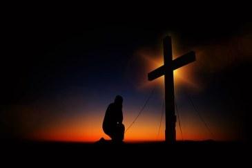cross, kneeling at foot of